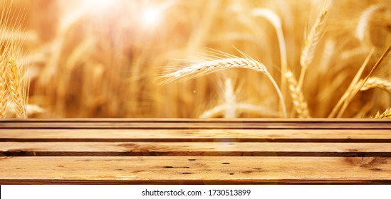 Golden wheat field in sunlight with empty wooden boards in front of it. Close-up with short depth of field. Natural landscape with ripe ears of corn for a nutritional concept.