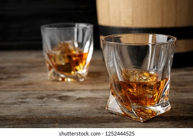 Golden whiskey in glass with ice cubes on wooden table. Space for text