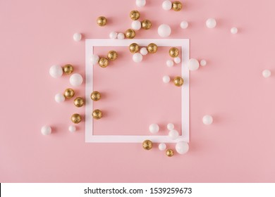 Golden and white glitter balls with paper card frame and pink background. Celebration minimal Christmas layout.