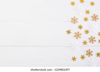 Golden and white snowflakes pattern on wooden white background. Space for text.