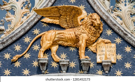Golden winged lion with parchment as roof decoration of Basilica San Marco in Venice, Italy