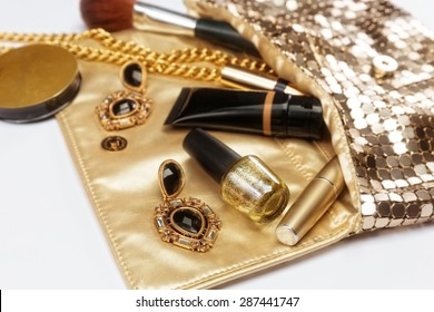 Golden woman accessories. Make up pieces, jewelry and shiny purse. Top view.