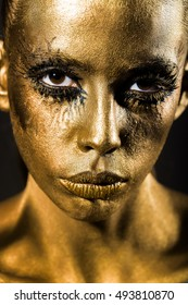 golden woman or girl has pretty face with makeup and body art metallized color and black eyes