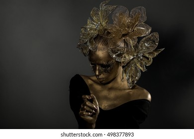 golden woman or girl has pretty face with makeup and body art metallized color with decorative flowers on head on black background, , copy space