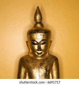 Golden wooden Buddha statue from Burma against yellow wall.