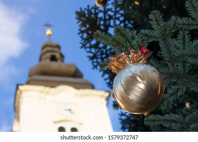 Golden wrapped Christmas balls under the pine tree and catholic church above it under the blue sky| outside