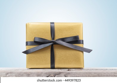 Golden wrapped gift box with black ribbon on a wooden table isolated on blue background