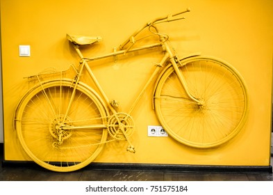 golden yellow bicycle as decoration and power socket and switch on the wall. old painted bicycle attached to the wall in art office toned to golden color. vintage bicycle on decorative color wall
