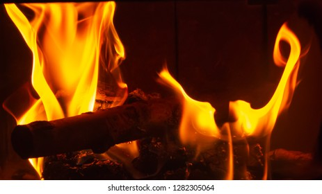 Golden yellow flames from a fireplace insert with logs nature photography