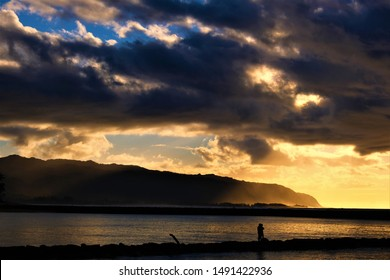 Golden yellow and moody sunset over the Pacific Ocean at Haleiwa Beach Park, Oahu HI with silhouettes of people watching the sunset from the lava rock wall.