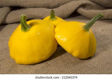 Golden yellow pattypan squash on a hessian / burlap background