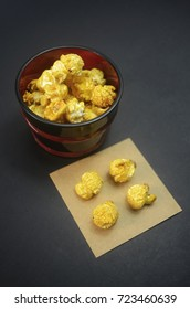 golden yellow popcorn inside a bowl and four pieces at small paper on white background