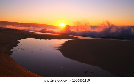 Golden yellow sunset on the North Shore of Oahu, Haleiwa Hawaii.  Waves crashing on shore sending up ocean water.  In the foreground a small lake of ocean water collected on shore.