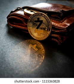 Golden Z Cash coin leaning against a leather wallet on a plain surface
