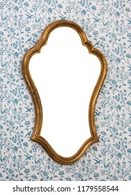 Golden-framed mirror on wallpapered wall with white copy space.