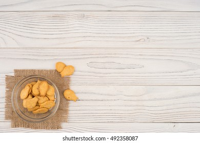 Goldfish cracker in a glass bowl on a white wooden table. Top view.