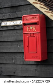 Goldhanger/ United Kingdom - March 19 2017: Bright red mailbox with symbols E and R and crown between them, on the wooden wall. Nr 16 Fish Street label.