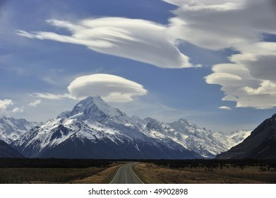 Gold-mounted road with Mount Cook rimmed with puffs of white cloud