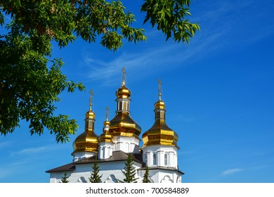 Gold-plated domes of Orthodox church through green foliage against the blue sky. Russia