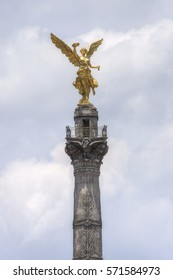 Gold-plated sculpture representing the Angel of Independence at top of victory column on Mexico City's famous Paseo de la Reforma on cloudy day