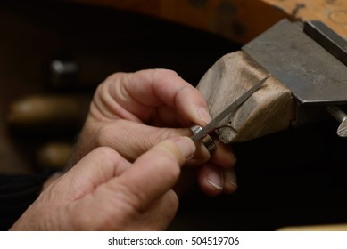A goldsmith files the cut edges of a gold ring before soldering it together at a smaller size