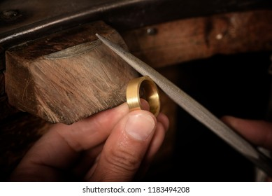 goldsmith hand holds a golden ring on the wooden workbench and works on it with a metal file, close up with copy space,  focus, narrow depth of field