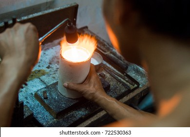 Goldsmith makes gold necklace and jewelry. gold melting process with gasoline burner in crucible.