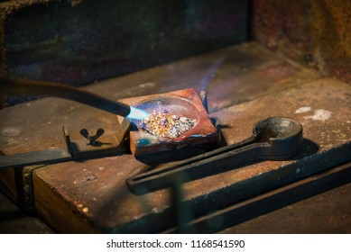 goldsmith melting gold and silver granules in a  crucible with a gas flame from a blowtorch in a jewelry, copy space, selected focus, narrow depth of field