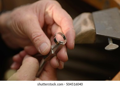 A goldsmith resizes a gold ring