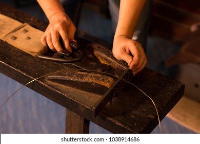goldsmith stretch a gold line on wooden working machine . process for make jewelry in factory .
