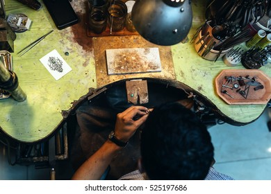 Goldsmith working on his bench, crafting jewelry