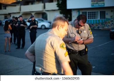 Goleta, California / USA - April 5 2014: Sheriffs deputy writing citations in Isla Vista (IV) during Deltopia weekend, a Spring party beside the University of California Santa Barbara (UCSB)