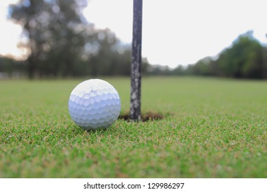Golf ball about to fall into the cup