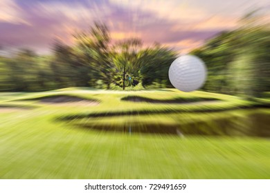 Golf ball is aiming to golf hole for hole in one. green grass field flag in the evening or in the morning time, the golden light of the sunset as background.Concept of Success for genius