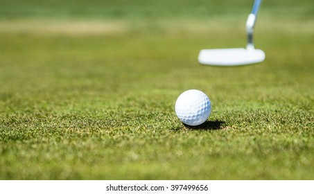 Golf ball approaching the hole with Putter in Background