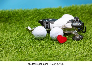 Golf ball and golf bag with love on green grass.