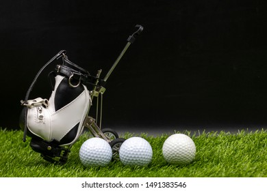 Golf ball and golf bag are on green grass
