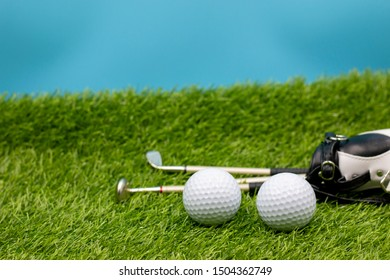 Golf ball and golf bags are on green grass