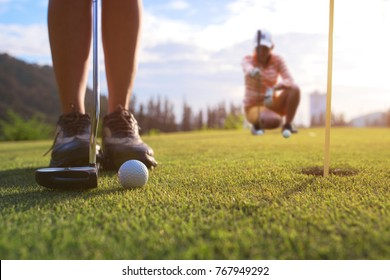 Golf ball being hit impact by the putt of player on the green with golfmate in attention checking putting line in background
