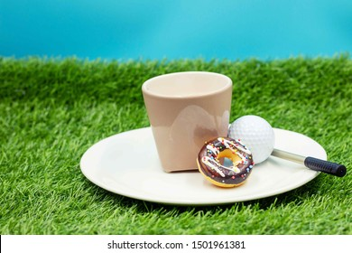 Golf ball is being served to golfer on the white plate for break at 19th hole clubhouse on green grass for crazy golfer