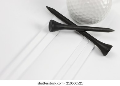 Golf ball with black tees on white pleats