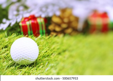 Golf ball with blurred Christmas present on green grass