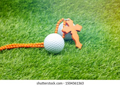 Golf ball and Christian cross are on green grass.