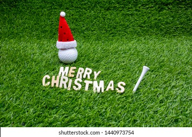 Golf ball with Christmas hat are on green grass. Merry Christmas to golfer.