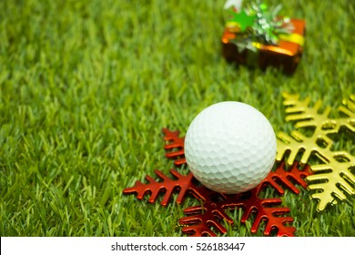 Golf ball with Christmas ornament on green background