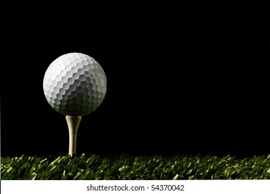 Golf ball close up on tee at night , black background with copy space on right