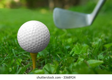 Golf ball close-up from the ground level with grass and putter