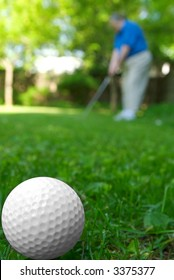 Golf ball close-up from the ground level with grass and golfer