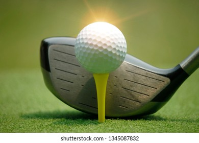 Golf ball and golf club in beautiful golf course with sunset background. close up of golf equipment  on green grass.