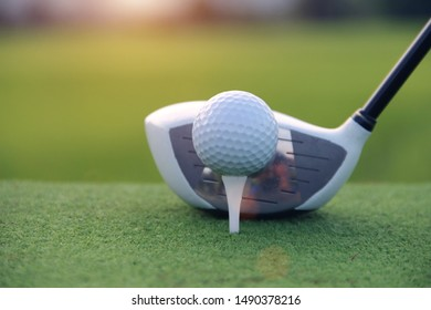 Golf ball and golf club in beautiful golf course at sunset background.